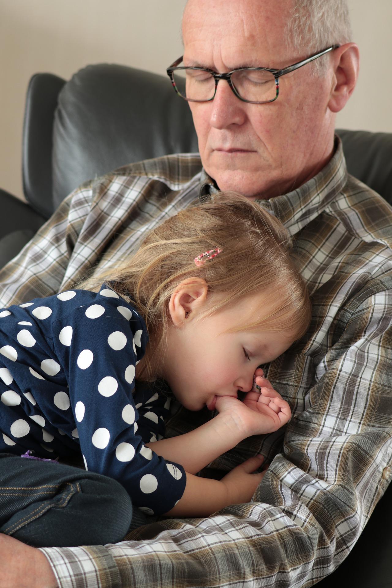 man asleep nursing young girl